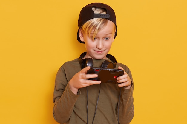Emotional and active little boy with blond hair, carrying his finger on screen of smartphone while playing his favorite online game