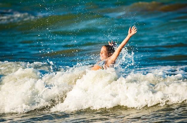 휴일 동안 화창한 여름 날에 폭풍우 치는 바다 파도에 튀는 감정적 인 활성 어린 소녀. 아이들과 함께하는 가족 휴가의 개념. 물과 원소를 사랑하는 사람들