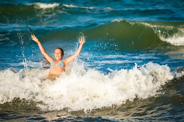 Эмоциональная активная маленькая девочка плещется в бурных морских волнах в солнечный летний день во время каникул. концепция семейного отдыха с детьми. любители воды и стихии
