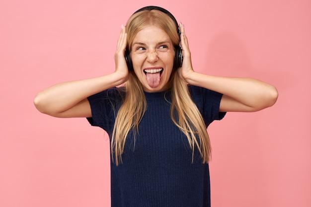 Эмоциональная очаровательная девочка-подросток наслаждается любимыми музыкальными композициями в беспроводных наушниках