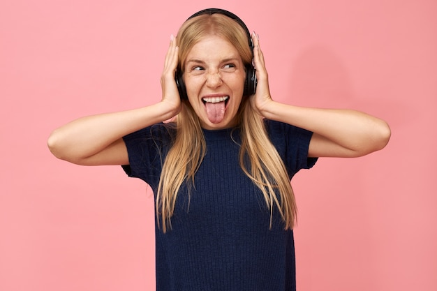 Ragazza adolescente adorabile emotiva che gode dei brani musicali preferiti in cuffie wireless