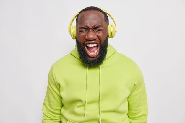 Emotivo uomo adulto con barba folta esclama ad alta voce ascolta musica in cuffie stereo wireless vestito con felpa con cappuccio isolato su muro grigio