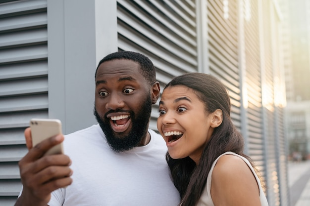 Emotional african american couple using smartphone shopping online, focus on man face