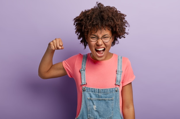 Emotional african american girl raises fist, exclaims from positive emotions, smirks face, dressed in pink t shirt and denim sarafan, stands against purple wall. we did together, congratulation!