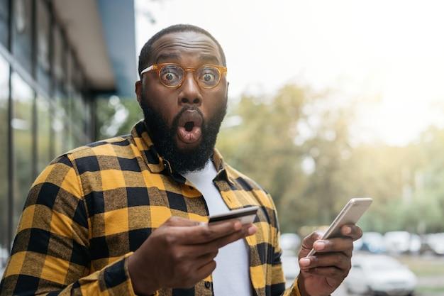 Эмоциональный афро-американский мужчина держит кредитную карту, делая покупки в интернете. эмоциональный фрилансер получает оплату