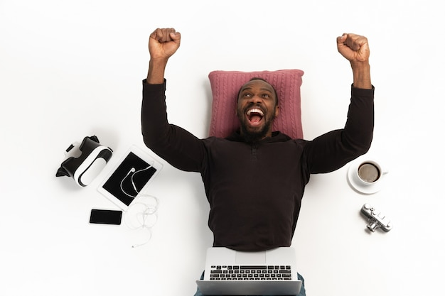 Emotional african-american man using laptop surrounded by gadgets isolated on white studio background, technologies. crazy winning