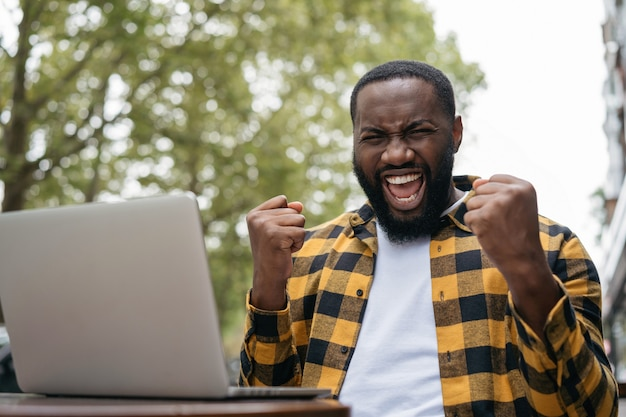 Emotional african american man win online lottery celebration success