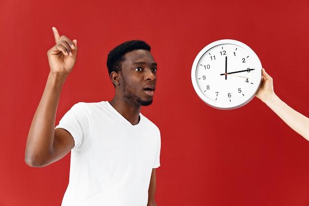 彼のハンドスタジオで身振りで示す時計の横にある感情的なアフリカ系アメリカ人
