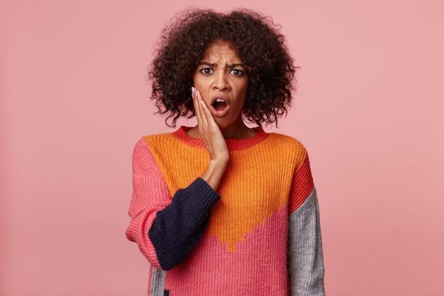 Emotiva donna afro-americana con acconciatura afro guardando qualcosa di terribile orribile terribile disgustoso, bocca aperta dallo shock, appoggiato le mani sul viso, indossa un maglione colorato, isolato sul rosa
