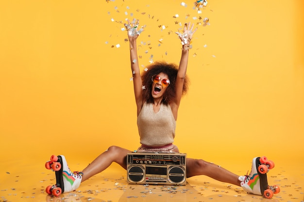Emotional african disko woman in retro wear and roller scates throwing confetti while sitting with boombox