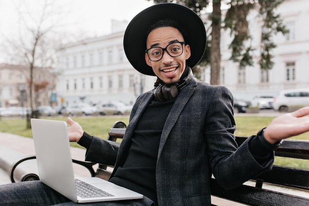 Emotional african student in glasses sitting on bench with laptop. outdoor photo of mulatto male freelancer in black attire working with computer.