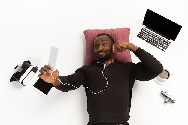 Emotional africanamerican man using phone surrounded by gadgets isolated on white studio wall.