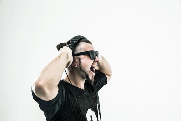 Эмоциональный и харизматичный диджей-рэпер с наушниками на свету