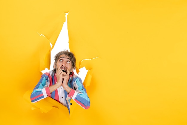 引き裂かれた黄色の紙の穴の背景で見上げる感情的で夢のような若い男