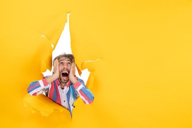 引き裂かれた黄色の紙の穴の背景で見上げる感情的で怖い若い男