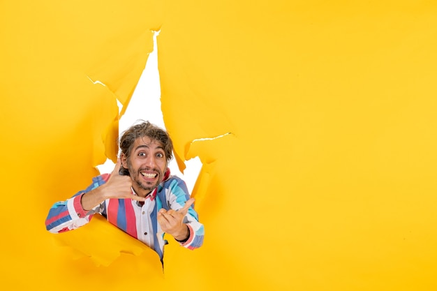 引き裂かれた黄色い紙の穴の背景で私をジェスチャーと呼んでいる感情的で笑顔の若い男