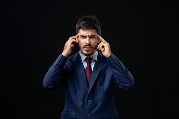 Эмоциональный молодой бородатый мужчина сосредоточился на чем-то на изолированной темной стене