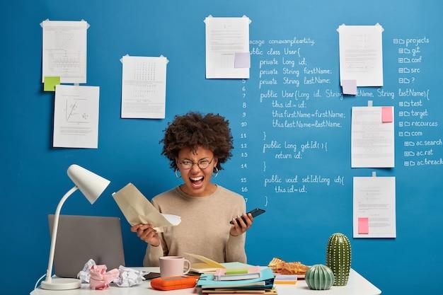 감정적 인 화가 아프리카 계 미국인 여성은 성공적인 프로젝트를하지 못해 좌절 한 종이 문서와 휴대 전화를 들고 있습니다.