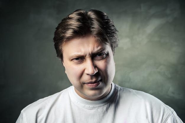 어두운 회색 배경 위에 감정적으로 화난 중년 남자
