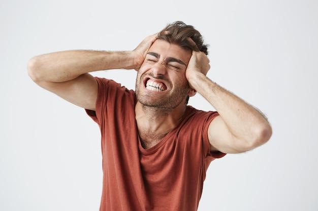 赤いtシャツを着て感情的に怒っている筋肉質の男が目をしっかりと閉じ、痛みや完全な不信感で叫び、手を頭に抱えています。否定的な人間の感情と感情