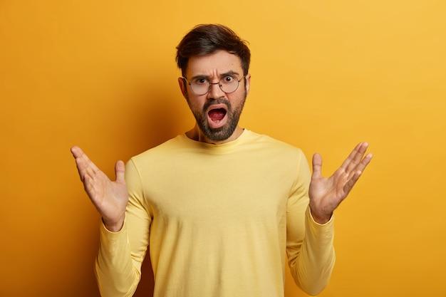 정서적 성가신 남자는 손바닥을 펼치고 분노로 외치고, 입을 벌리고, 부정적인 감정을 표현하고, 누군가에게 소리 지르며, 캐주얼 한 옷을 입고, 짜증이 나는 몸짓을하고, 분노한 표현을 가지고 있습니다.