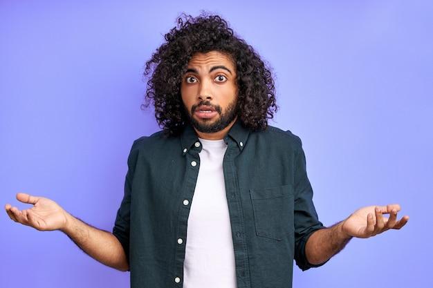 감정적 인 아랍 남성은 오해하고, 무언가에 반응하고, 팔을 벌리고, 몸짓을합니다. 격리 된 보라색 벽