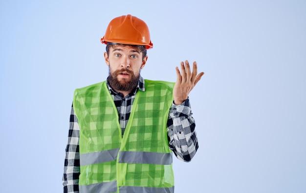 青い背景に彼の手でヘルメットと反射的な哀れなジェスチャーで感情的な建築家