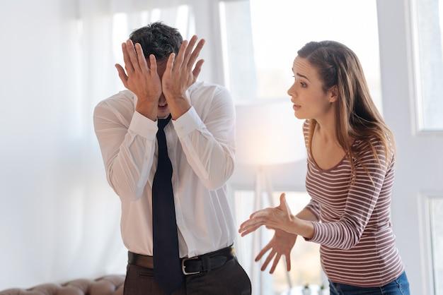 감정적 논쟁. 화가 난 아내의 불쾌한 말을 듣기를 거부하면서 두 손으로 얼굴을 닫는 감정적 피곤한 남자