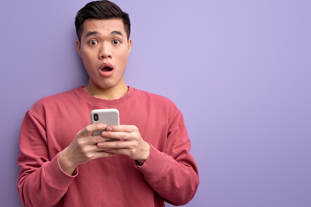 Emotional asian guy chatting with someone on smartphone, stand in shock by news