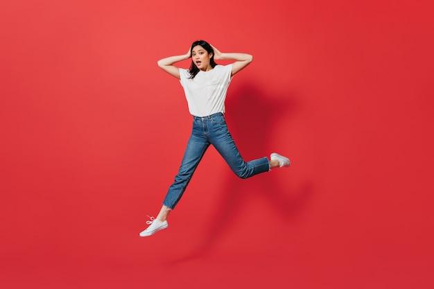 Donna asiatica emotiva in jeans che salta sulla parete rossa