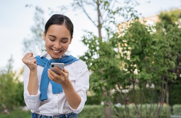 휴대 전화를 사용하는 감정적 인 아시아 여성, 디지털 화면을보고, 그녀는 온라인 복권, 축하 성공