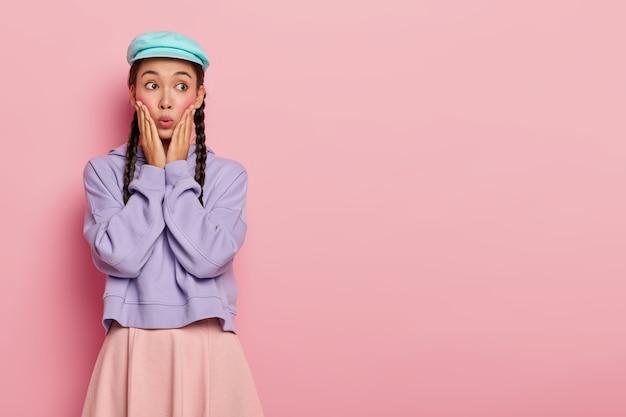 見事な外観を持つ感情的なアジアの女性は、重要なことを忘れて、自由空間に目をそらし、スタイリッシュな服を着て、ピンクの壁にポーズをとる