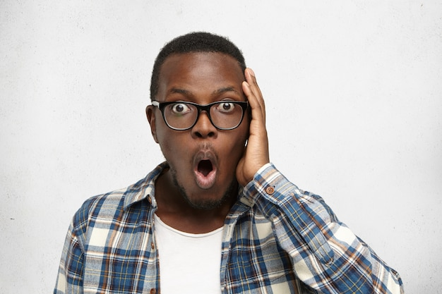 Emotional astonished oyung dark-skinned man in glasses and checkered shirt touching head in full disbelief, surprised and shocked with positive unexpected news. human face expressions and emotions
