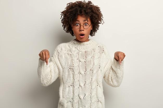 Эмоциональная привлекательная афроамериканка с потрясенным выражением лица указывает вниз, носит очки и джемпер, модели над белой стеной. концепция рекламы. посмотрите вниз.