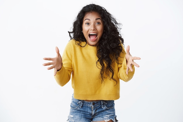 Emotional attractive curly-haired girl look alarmed, shouting and raising hands up stare shocked and troubled as watching something fragile fall, white wall