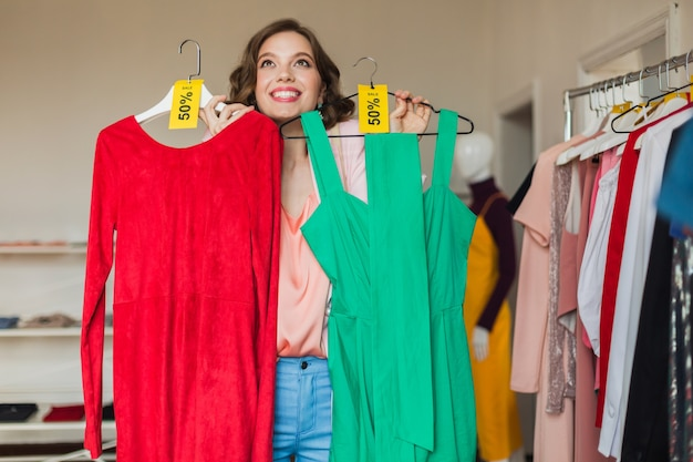 Emotional attractive happy woman holding colorful dresses in clothing store