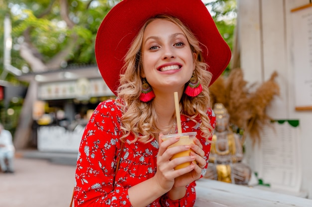 Emotional attractive stylish blond smiling woman in straw red hat and blouse summer fashion outfit drinking natural fruit cocktail smoothie