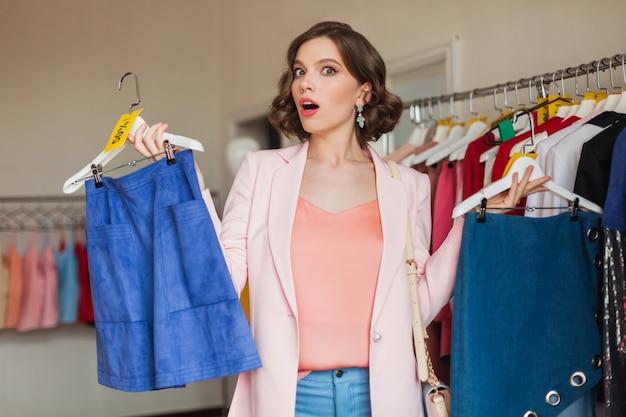 衣料品店でハンガーにアパレルを保持している感情的な魅力的な女性