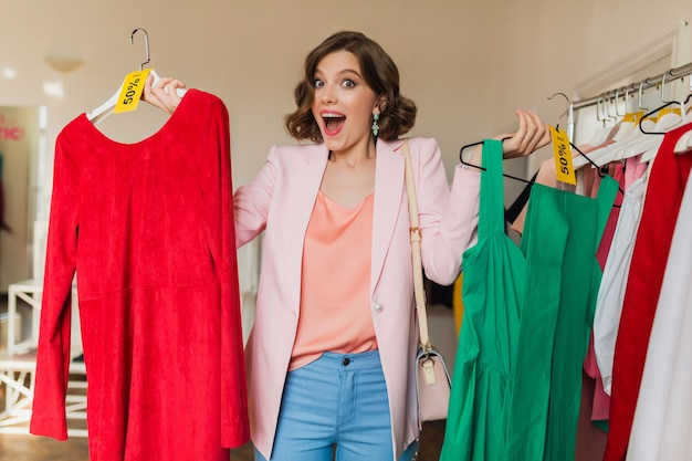 Emotional attractive woman holding colorful dresses on hanger in clothing store