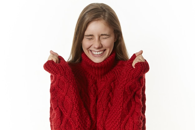 Эмоциональная привлекательная молодая женщина в уютном пуловере восклицает и сжимает кулаки от волнения и закрывает глаза, пребывая в восторге от неожиданного успеха. красивая девушка взволнованно жестикулирует