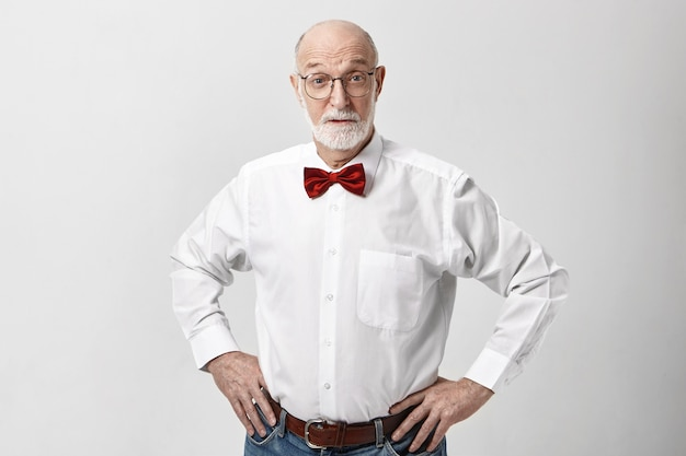 Maschio maturo con la barba lunga calvo emotivo in elegante abbigliamento alla moda e occhiali che alzano le sopracciglia