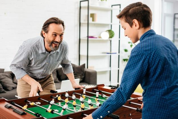 Эмоциональный бородатый активный мужчина улыбается и внимательно смотрит на сына-подростка перед ним, играя в настольный футбол