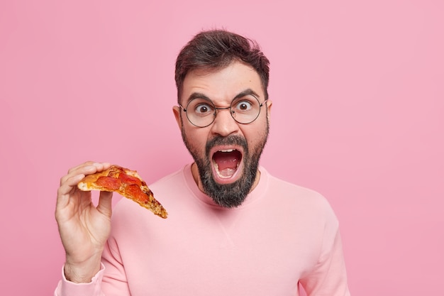 Emotional bearded adult man screams loudly holds slice of tasty appetizing pizza eats fast food for snack dressed in casual clothes