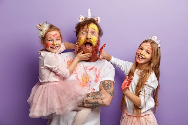 Emotional bearded busy father spends time with two naughty daughters who leave palm prints on his beard and clothes, learn how to paint, dressed in festive clothes, stand indoor. so colorful!