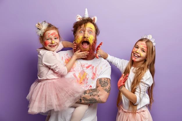 Эмоциональный бородатый занятой отец проводит время с двумя непослушными дочерьми, которые оставляют отпечатки ладоней на его бороде и одежде, учатся рисовать, одеваются в праздничную одежду, стоят в помещении. так красочно!