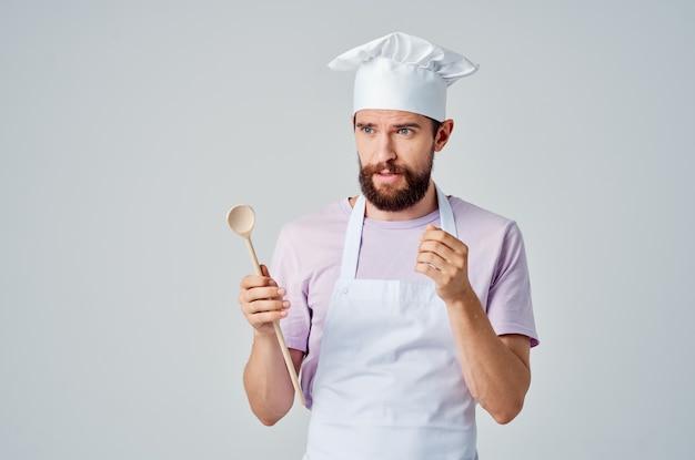 頭に帽子をかぶった感情的なひげを生やしたシェフは、彼の手にスプーンを持っていますレストランの専門家