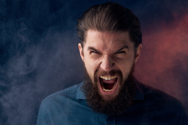 感情的なひげを生やした男の怒っている表情のシャツの煙が背景にあります。