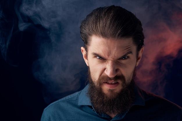 感情的なひげを生やした男の怒っている表情のシャツの煙が壁に