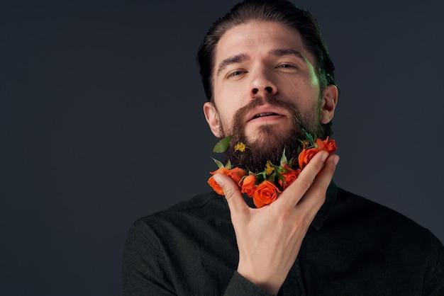 Эмоциональный бородатый мужчина цветы романтика крупным планом темный фон. фото высокого качества