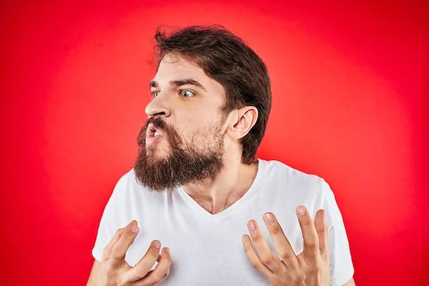 Эмоциональный бородатый мужчина жестикулирует руками в белой футболке агрессии и недовольства красной стеной.